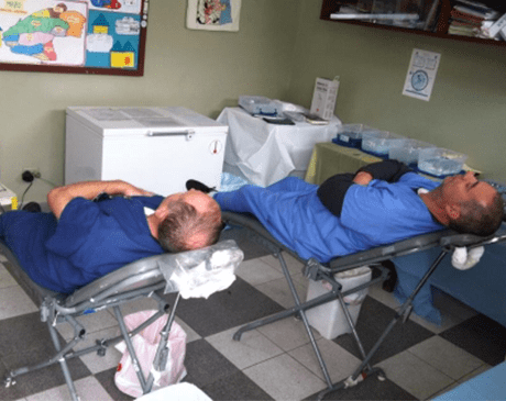 Two dentists resting after providing dental treatment on mission trip