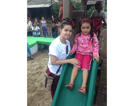 Dental team member and child on a playground