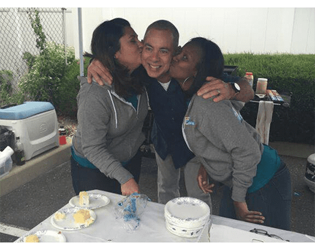 Two dental team members kissing dentist's cheek at community event