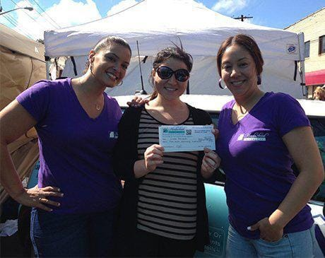 Two team members and dental patient at community event