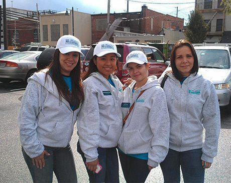 Four dental team members wearing matching sweatshirts at community event