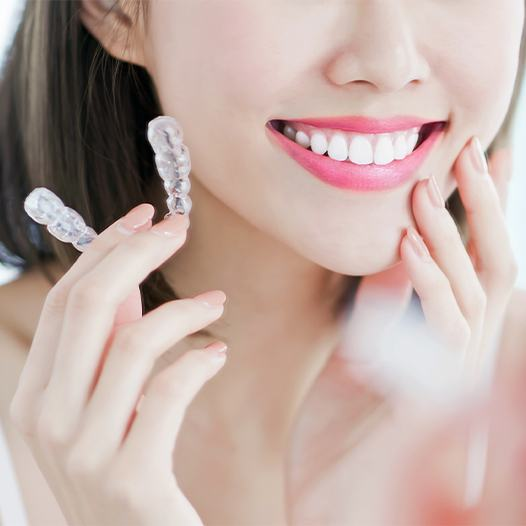 Smiling woman holding her Invisalign tray