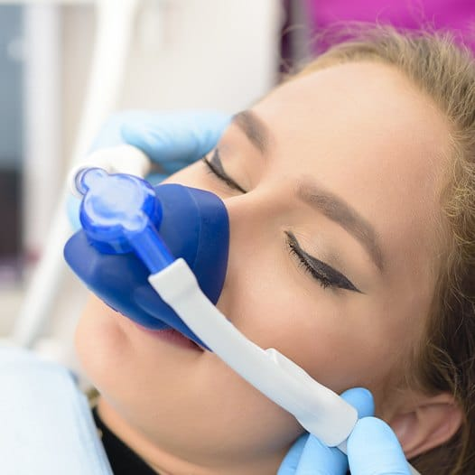 Woman with nitrous oxide sedation dentistry nasal mask in place
