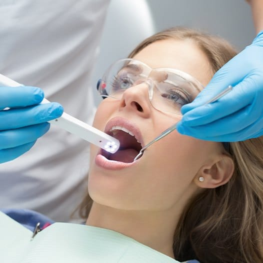 Dentist using intraoral camera to capture images of a patient's smile