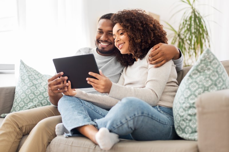 Couple smiling while looking at tablet
