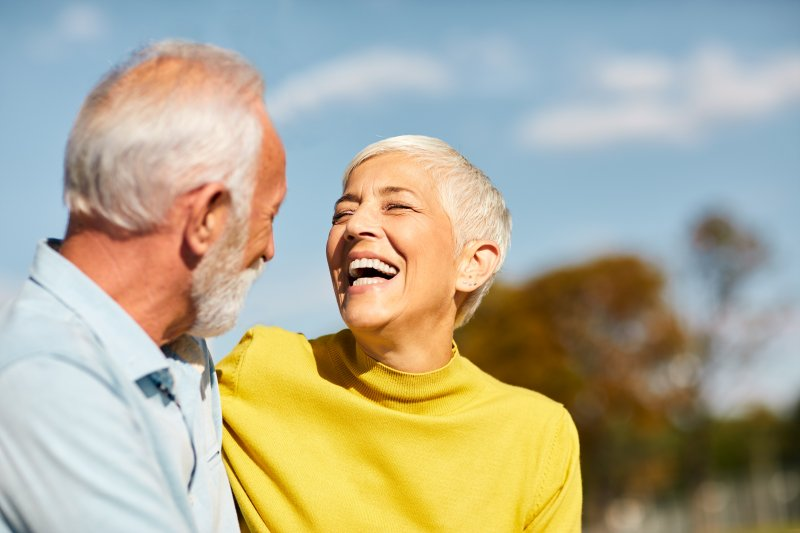 Older couple with dental implants smiling outside